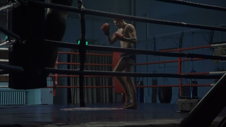 Man training with punching bag in the ring