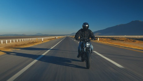 Man traveling by motorcycle on an empty road