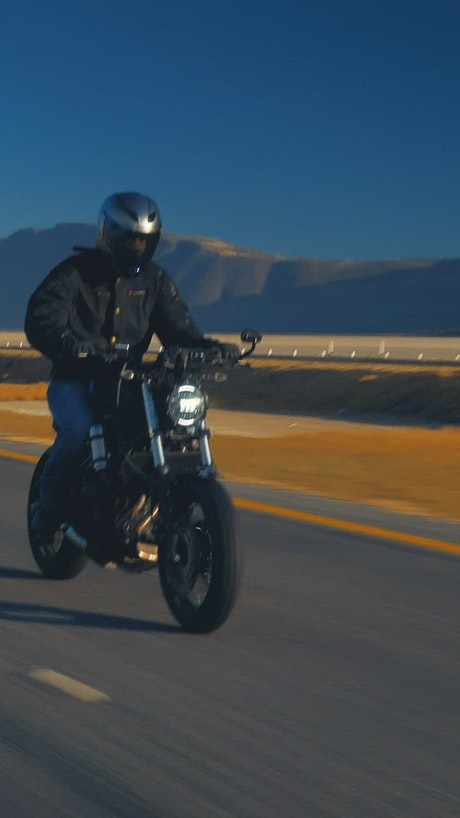 Man traveling fast by motorcycle on a road
