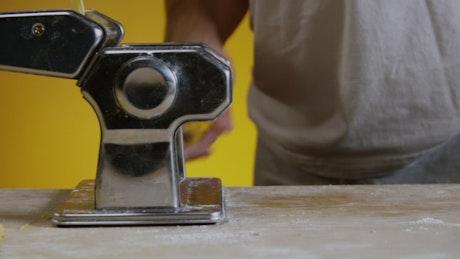 Man turning a pasta maker