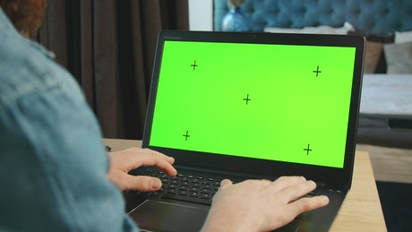 Man types on greenscreen laptop in bedroom