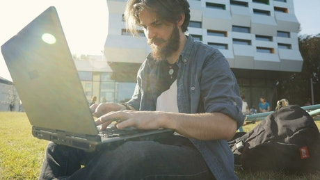 Man typing on laptop outside smiles in triumph