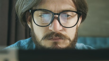 Man typing on laptop reflected in glasses