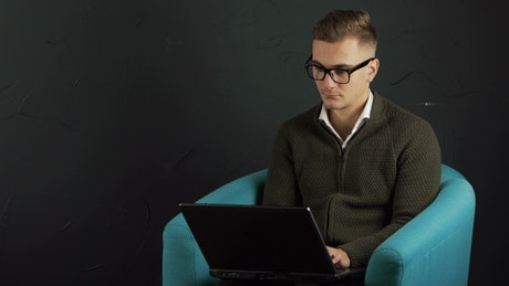 Man typing on laptop with black background