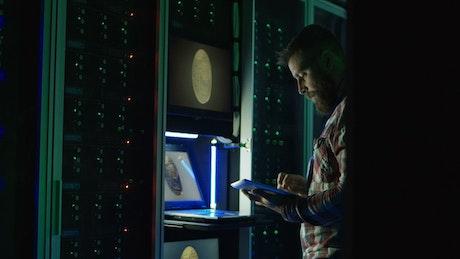 Man using a laptop in a dark room data center