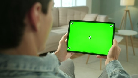 Man using green screen tablet in neutral living room