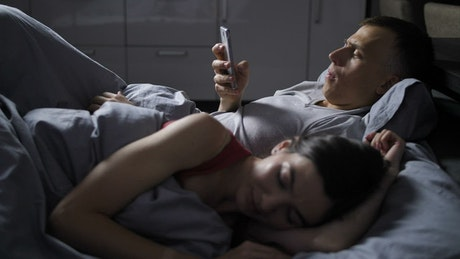 Man using his phone while his wife sleeps