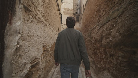 Man walking along an old narrow alley, tracking