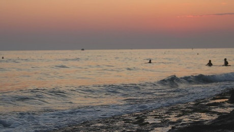 Man walking along the shore of a beach at sunset