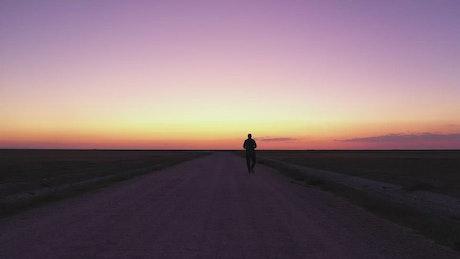 Man walking down an empty road