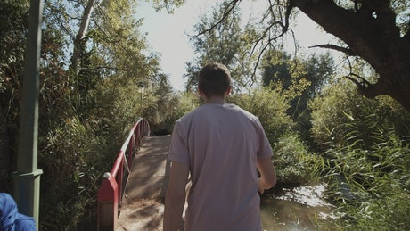 Man walking on a bridge in a park, tracking shot
