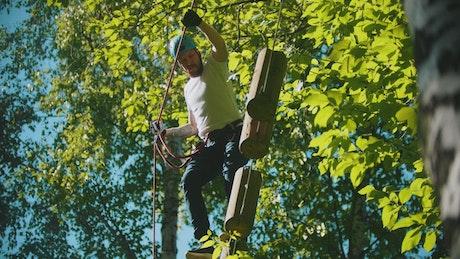 Man walking on floating logs in the woods