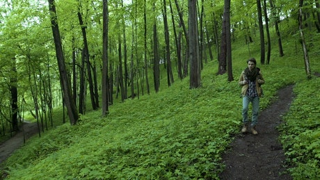 Man walking through the path in a green forest