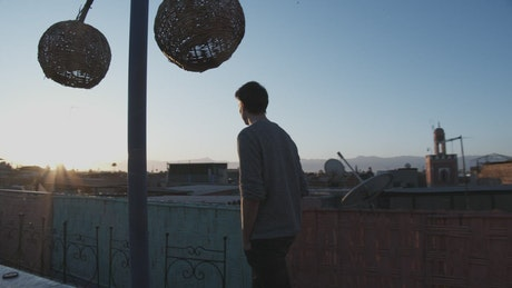 Man walks on the rooftop with sunrise view