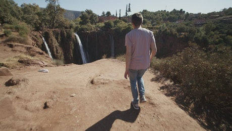 Man walks to a canyon in nature with waterfalls