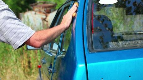 Man washing a blue car