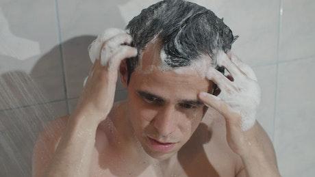Man washing hair in bathroom