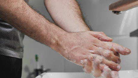 Man washing his hands with soap, detailed view