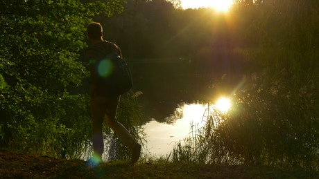 Man watching the sunset by the river