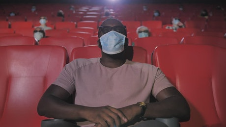 Man wearing a mask in a cinema