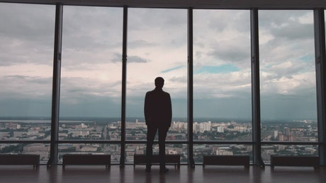 Man wearing a suit looking out towards a city