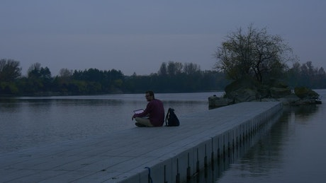 Man with a laptop on the shore of a lake at dusk