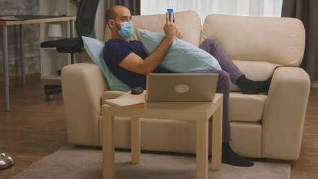 Man with coronavirus chats on social media from couch