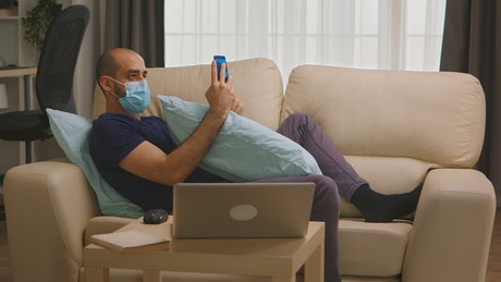 Man with coronavirus on sofa with mobile phone