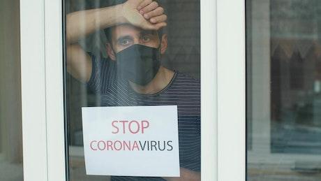 Man with coronavirus sign in the window