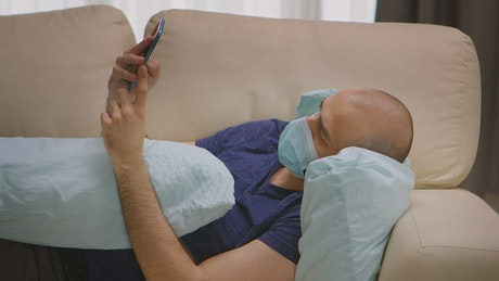 Man with Covid-19 lays on sofa with mobile phone