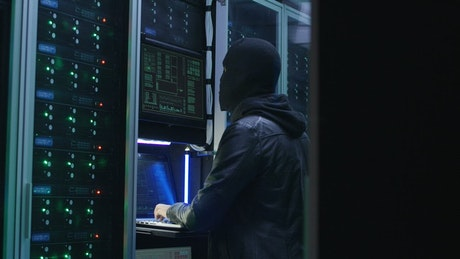 Man with face mask hacking a data center
