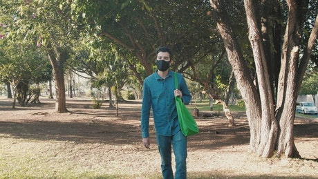 Man with face mask in a park after shopping