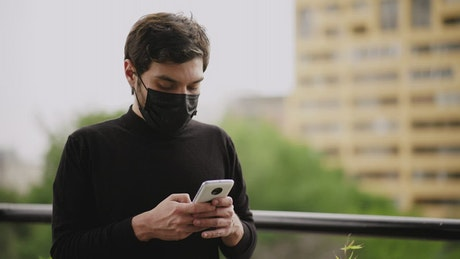 Man with face mask sending audios by cell phone