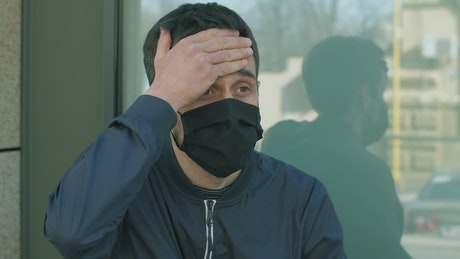 Man with fever in the street wearing mask