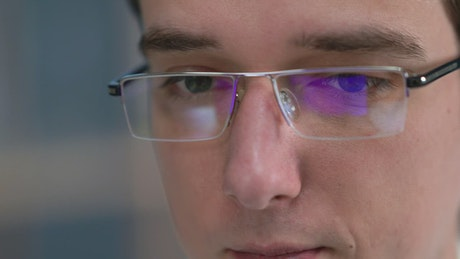 Man with glasses looking at monitor