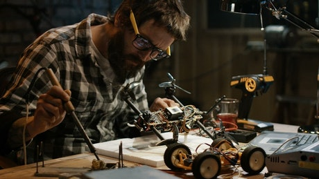 Man with glasses soldering a drone in the garage
