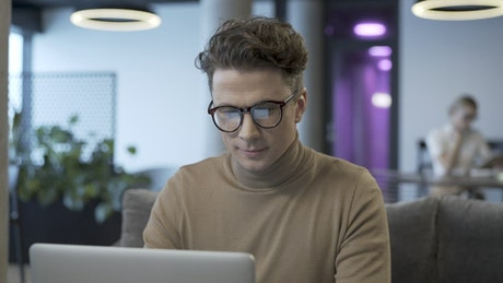 Man with glasses working on a laptop