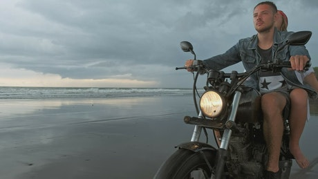 Man with his girlfriend riding motorcycle on beach