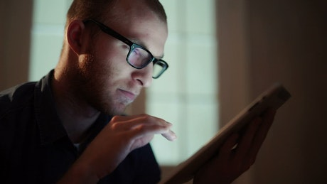 Man with insomnia scrolls through tablet