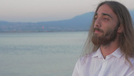 Man with long hair lost in thought