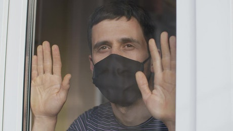 Man with mask looks longingly from his window