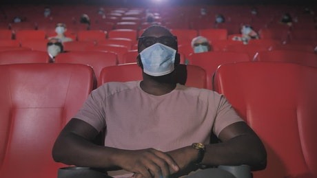 Man with mask sitting in a movie theater