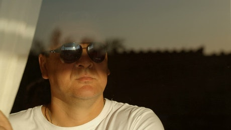 Man with sunglasses looking out of a hotel window