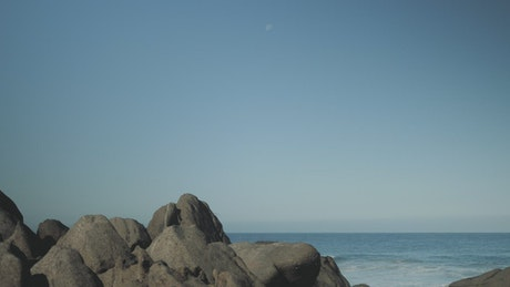 Man with surfboard stands on boulders