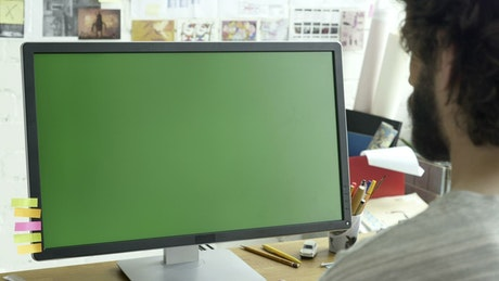 Man working on a computer with a green screen