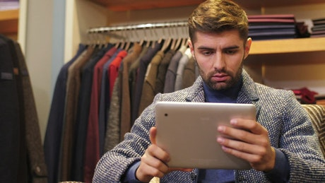 Man working on a tablet in a suit store