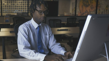 Man working on computer in an office at night