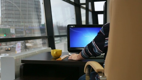 Man working on his computer by the window