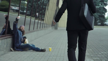 Man working on the street gives money to homeless