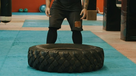 Man working out in a gym with a big tire